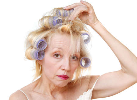 bad hair day: A blonde woman curling her hair with lavender curlers.  Bad hair day.