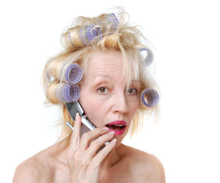 A blonde woman with lavender curlers in her hair, talking on her cell phone.  Bad hair day. photo