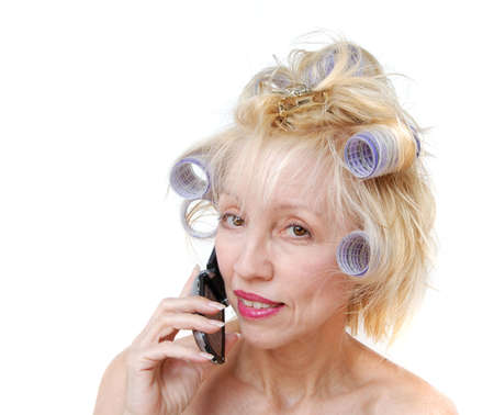 A blonde woman with lavender curlers in her hair is talking on her cell phone. photo