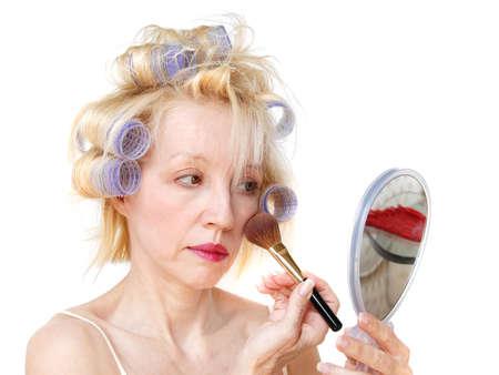primp: Una donna del blonde con i bigodini della lavanda in suoi capelli sta applicando la sua guancica arrossisce con una spazzola mentre esaminava uno specchio. Archivio Fotografico