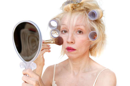 primp: A blonde woman with lavender curlers in her hair applies her cheek blush with a makeup brush while holding a mirror in her hand.