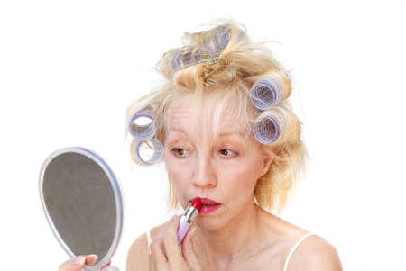 primp: Una donna del blonde con i bigodini della lavanda in suoi capelli esamina il suo specchio della mano ed applica il suo rossetto. Archivio Fotografico