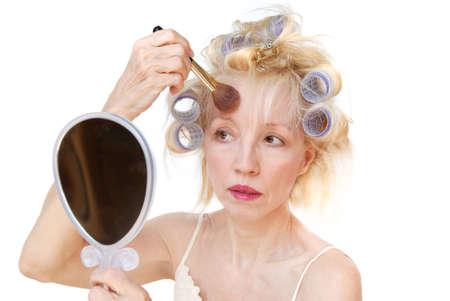 primp: Una donna bionda con lavanda curlers nel suo volto si applica capelli in polvere e arrossire di fronte a lei, mentre cercando in mano uno specchio.