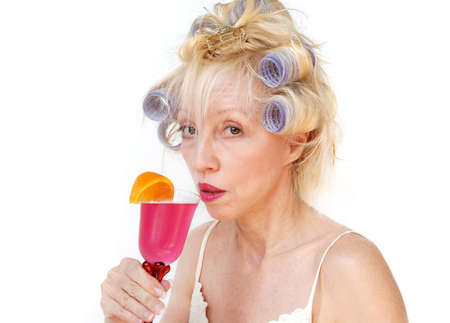 A blonde woman with lavender curlers in her hair sips a refreshing drink at the salon. photo