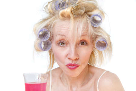A blonde woman with lavender curlers in her hair sips a drink at the salon and makes a sour facial expression. photo