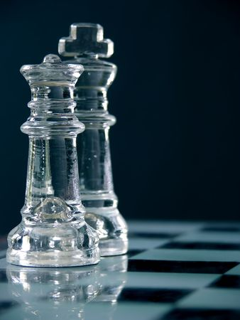 King and queen on the chess board, macro image of glass pieces.  Shallow dof, focus on the queen in front. photo