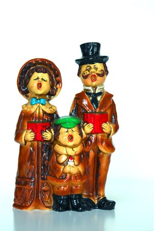 carols: Vintage Christmas Carolers from the early 1900s.  Man, woman and child holding songbooks and singing. White background and reflection at bottom.