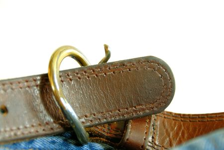 Leather Belt - Leather belt on a pair of jeans, shallow depth of field, over white.