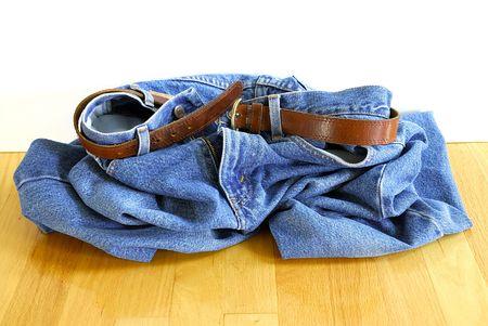 dropped: Caiga sus pantalones vaqueros - un par de pantalones vaqueros azules con una correa de cuero est� en un mont�n en el piso. Foto de archivo