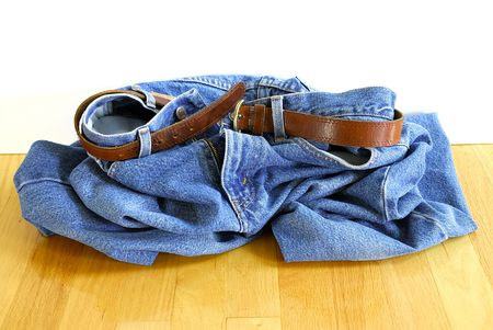 scrunch: Drop Your Jeans - a pair of blue jeans with a leather belt is in a heap on the floor.