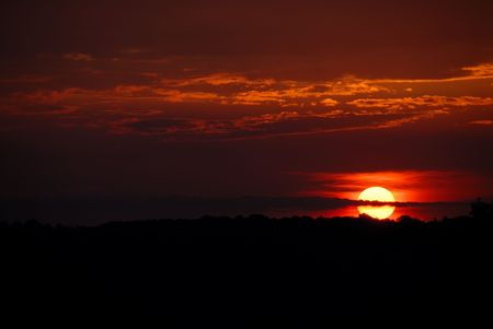 Orange Sunset - The sun sets in a blaze of orange and rust colors into  the black silhouette of the hillside.