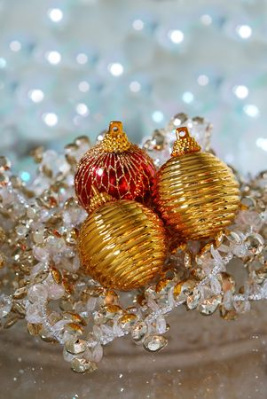 decora: Christmas Tree Ornaments - Red and gold Christmas tree ornaments and crystal garland on a reflective surface. christmas, holiday, ornament, ball, bauble, bow, gold, red, beads, balls, round, shape, fabric, material, netting, tradition, traditional, decora