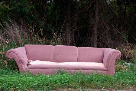 destroyed: Roadside Sofa - Ein altes Sofa warf sich auf die Seite der Stra�e in den W�ldern entlang einer Landstra�e.  Lizenzfreie Bilder