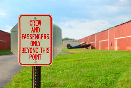 beyond: Airport Sign - Crew And Passengers Only Beyond This Point - a security  sign at a small airport at the entrance to the plane and hangar.