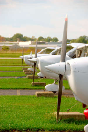 Small Plane Props - The propellers and noses of cessna skyhawk airplanes parked and tethered at a small airport.   Stock Photo