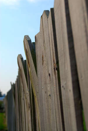 stockade: Stockade Fence - Wooden and warped, a stockade privacy fence guards the property. Shallow depth of field showing perspective.