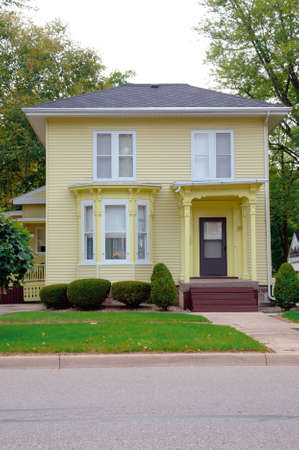 Yellow Victorian House - A yellow wood siding Victorian style house in a small town on the main street.  photo