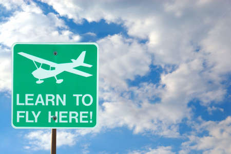 Airport Sign - Learn To Fly Here - with the cloudy sky as a background.   Stock Photo