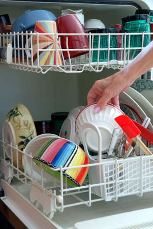 wash dishes: Washing Dishes - A female hand is shown loading dishes into the dishwasher.  Stock Photo