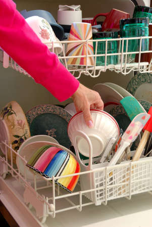 shown: Washing Dishes - A female hand is shown loading dishes into the dishwasher.  Stock Photo
