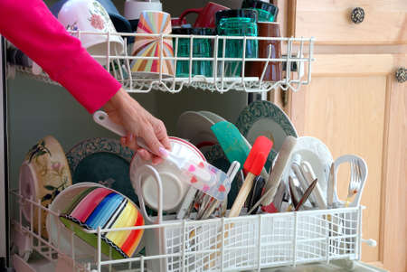 Washing Dishes - A female hand is shown loading dishes into the dishwasher.  photo