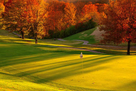 golf flag: Sunset at the Golf Course - The sun sets on a putting green at the golf course in Autumn.