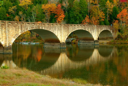 upstream: Fall colors surround a historic bridge, built in 1930, reflected in the Cumberland River just upstream of the Cumberland Falls in Kentucky, USA. Stock Photo
