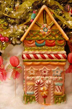 casita de dulces: Una casa de caramelos y chupetines sentarse en espumosos falso debajo de la nieve un �rbol de Navidad en la �poca de las fiestas.
