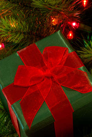 gossamer: A green fabric wrapped gift with a bright red gossamer ribbon and bow sits among the branches of a lighted christmas tree. Stock Photo