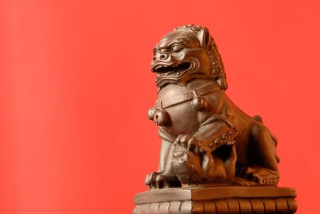 protects: Chinese Foo Dog - A female fu dog has a single cub under her left paw and protects those dwelling inside their home.  Stock Photo
