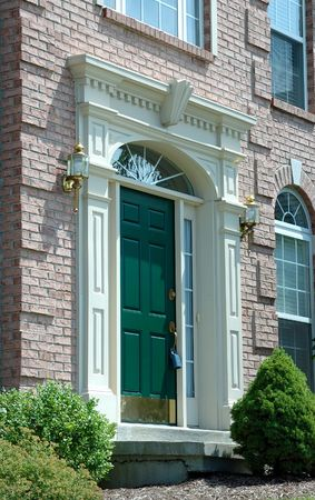 lockbox: Entry With Lock Box - Front entry door to a large brick home in the suburbs with a realtor lock box on the doorknob..