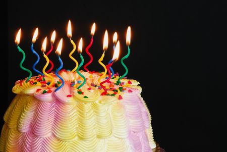 textspace: Lighted Birthday Cake - Burning candles on a pink and yellow iced birthday cake in front of a black background.  Stock Photo