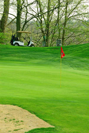 atop: Golf Course In Springtime - a golf cart sits atop a hill behind the flag.