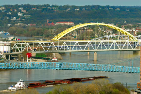 maneuvering: River Barge - A barge pushes up river maneuvering under the many colorful bridges spanning the Ohio River between the cities of Cincinnati Ohio and Covington Kentucky.