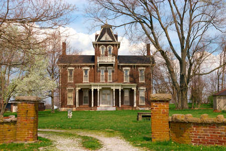 house gables: A typical two story brick home in the country that was built in the 1800s.  This house is built in Kentucky, USA.