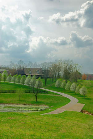 grassy knoll: Kentucky Farm On A Stormy Day -  A winding road lined with flowering pear trees leads to a Kentucky farm house on a grassy knoll as storm clouds gather overhead in preparation for a springtime rain shower.  Stock Photo