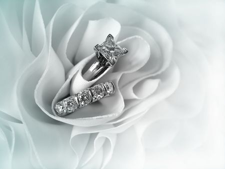 Beautiful diamond wedding ring set displayed in the folds of the fabric of a wedding gown. Space for copy.          Stock Photo