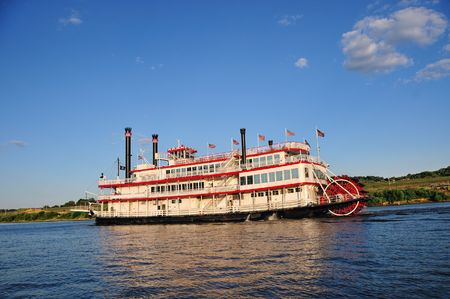 paddle wheel: A paddle wheel boat cruising up the Ohio River on a warm summer day.