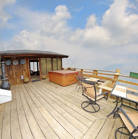 A deck with a hot tub and tables high up with a sky view.  Cabin in the sky, wide angle fisheye view.