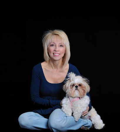 Portrait of a 58 yr old woman and her Shih Tzu dog on a black background.