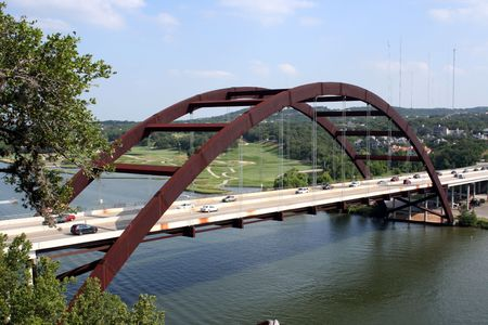 A shot of the Austin 360 Bridge on a clear calm day.  There was some traffic, but it was not too bad on the bridge.  In the distance is the golf course.  You can also see the radio towers in the background.  This is a very pretty picture of the bridge and