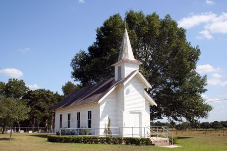 A small rural church in Texas.  There is a cemetary and a large oak tree behind the church. photo
