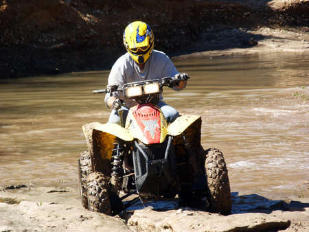 atv: A shot of a young man running some muddy trails on his ATV. Stock Photo
