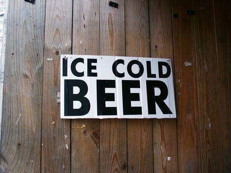 """posting: Un  """"hielo cerveza fr�a """" signo colgando de una pared de madera."""