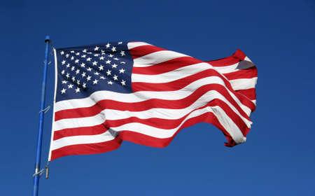 banderas america: Una bandera americana flaping audazmente en el viento.