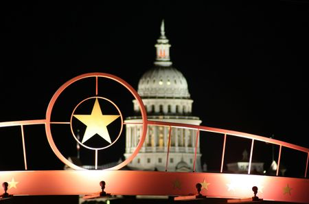 A shot of the star of Texas with the Texas State Capitol Building in the background.