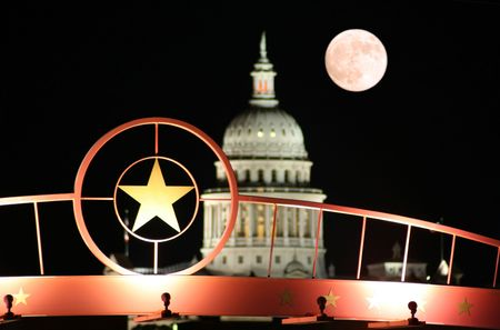A shot of the star of Texas with the Texas State Capitol Building and the moon in the background. Stock Photo
