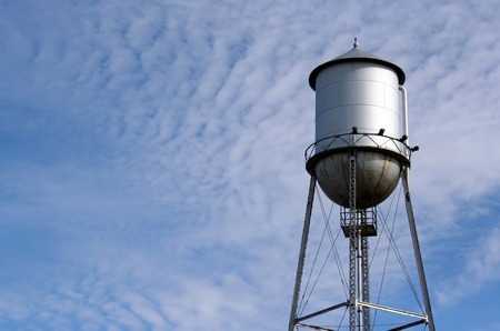 the water tower: A water tower against a cloudy blue sky.  Lots of space for copy. Stock Photo