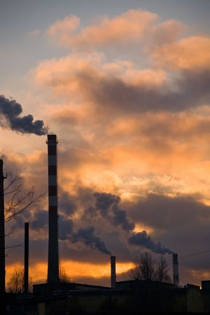 Pipes of factories on a background of a sunset in industrial area of St.-Petersburg photo