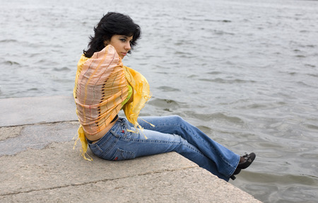 muffle: lonely woman sitting by the river muffling up in the shawl Stock Photo